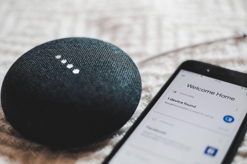 Symbolbild Smart Home: Zu sehen ist ein kleiner Lautsprecher und ein Smartphone, welches den Lautsprecher steuert.